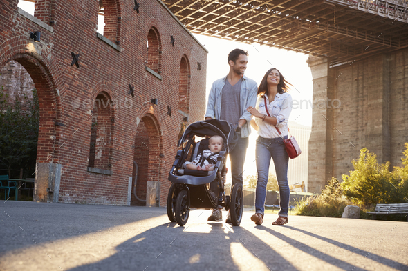 Young family with a daughter taking walk on a street - Stock Photo - Images
