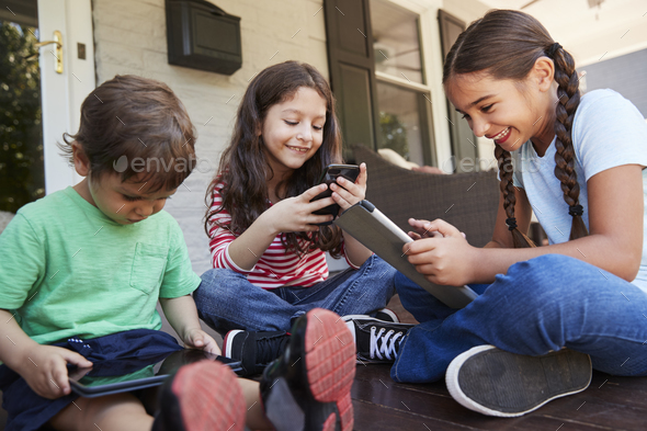 Group Of Children Sit On Porch Playing With Digital Devices - Stock Photo - Images