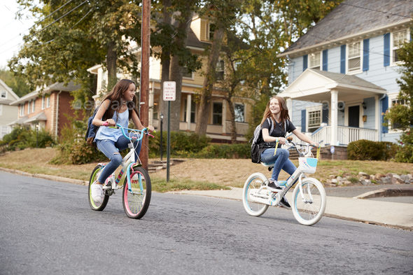 Two teen girlfriends ride past on bikes in a quiet street - Stock Photo - Images