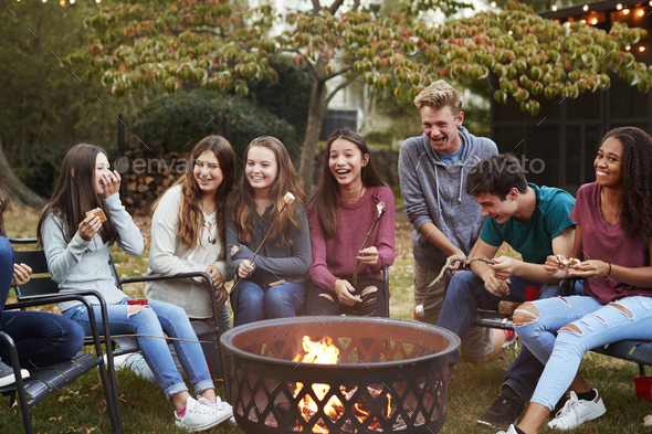 Teenage friends sit round a fire pit toasting marshmallows - Stock Photo - Images