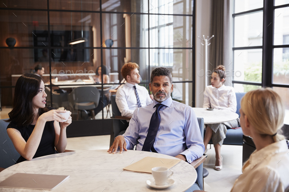Business colleagues talking at their office cafe - Stock Photo - Images