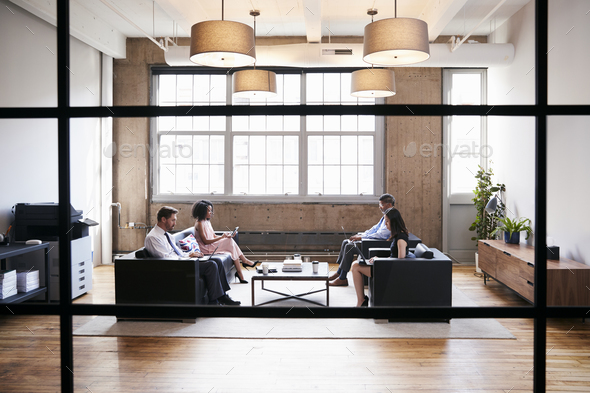 Business people in lounge meeting area, seen through window - Stock Photo - Images