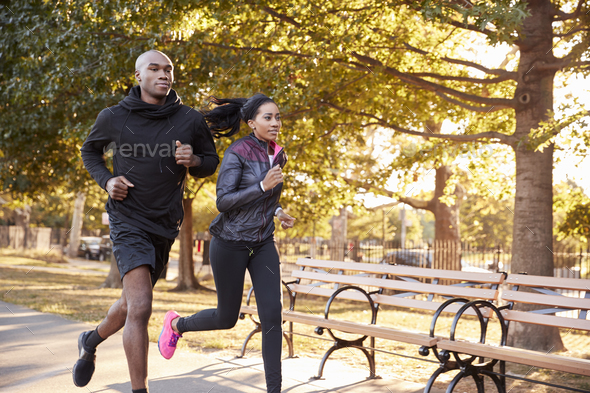 Young black couple jogging in a Brooklyn park, three quarter length - Stock Photo - Images