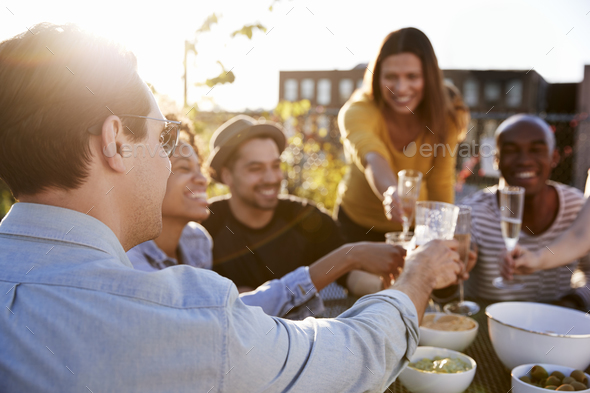 Friends making a toast on a New York rooftop, close up - Stock Photo - Images