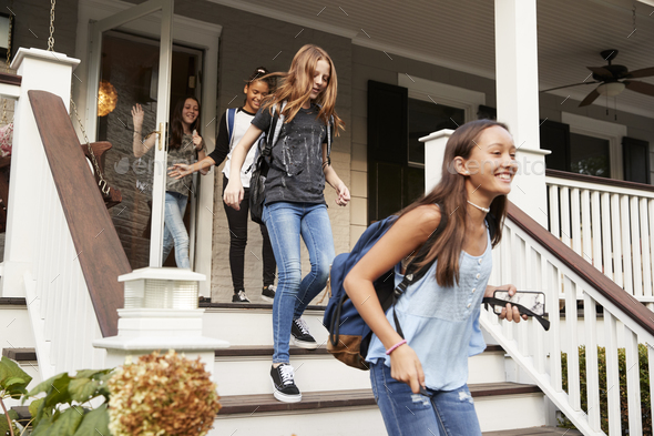 Four teen girls leaving house with school bags - Stock Photo - Images