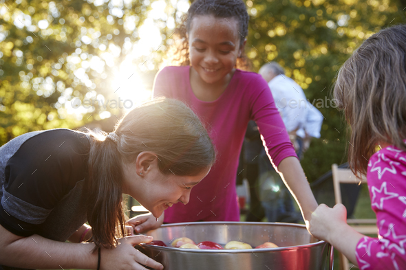 Young girls laugh while apple bobbing at a backyard party - Stock Photo - Images