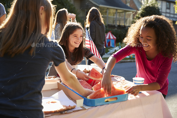 Girls serving themselves watermelon at a block party - Stock Photo - Images