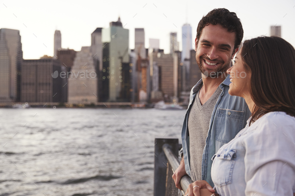 Young couple standing on quayside, side view - Stock Photo - Images