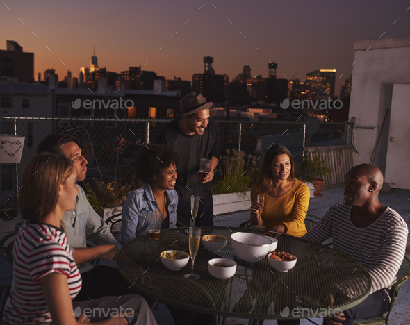 Adult friends talking at a table on a rooftop, evening - Stock Photo - Images