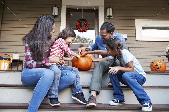 Family Carving Halloween Pumpkin On House Steps - Stock Photo - Images