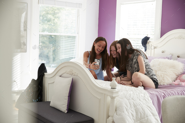 Three girlfriends sitting on a bed using a smartphone - Stock Photo - Images