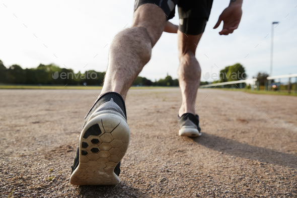Low section of male runner's legs ready to run at a track - Stock Photo - Images