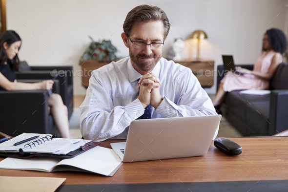Businessman using laptop at desk, colleagues in background - Stock Photo - Images