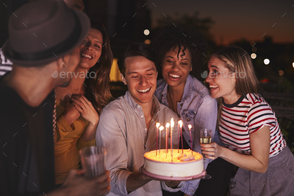 Young adults celebrating with a birthday cake on a rooftop - Stock Photo - Images