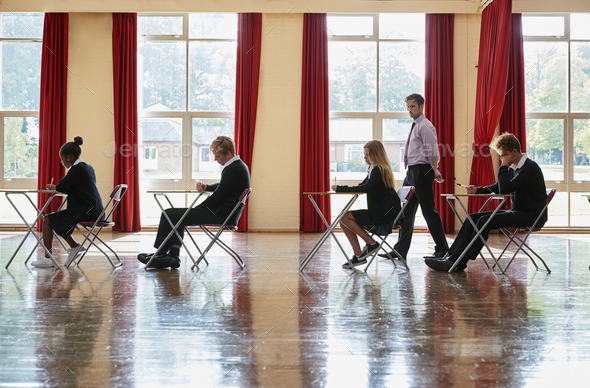 Teenage Students In Uniform Sitting Examination In School Hall - Stock Photo - Images