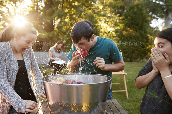 Friends watch teenage boy apple bobbing at garden party - Stock Photo - Images