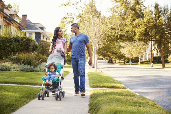Couple Push Daughter In Stroller As They Walk Along Street - Stock Photo - Images