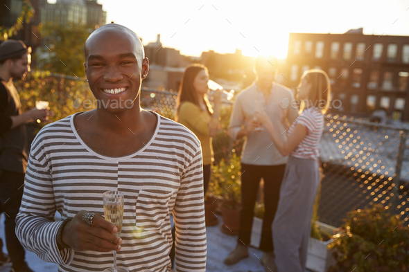 Young man holding glass at a rooftop party smiling to camera - Stock Photo - Images