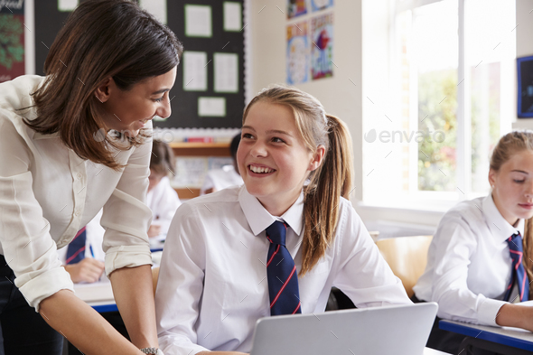 Female Teacher Helping Pupil Using Computer In Classroom - Stock Photo - Images
