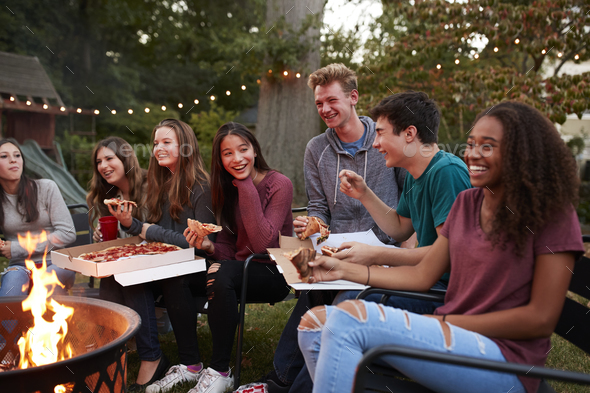 Teenagers at a fire pit eating take-away pizzas, close up - Stock Photo - Images