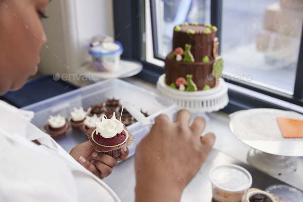 Black woman preparing food in a bakery, over shoulder view - Stock Photo - Images
