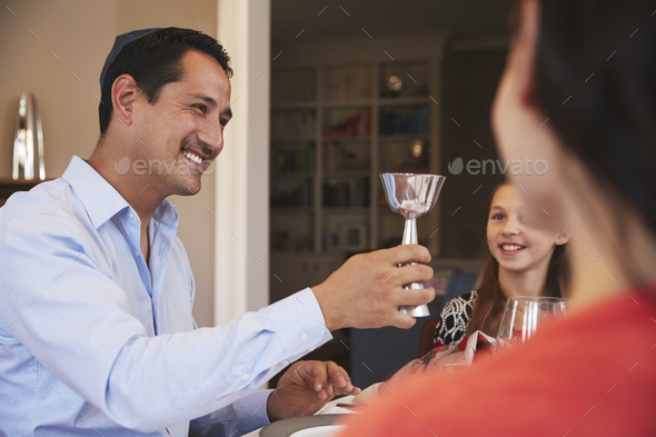 Jewish man holding kiddish cup blesses family at Shabbat - Stock Photo - Images