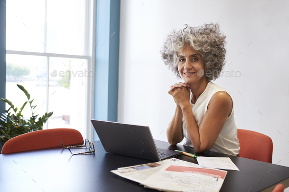 Middle aged woman working in an office smiling to camera - Stock Photo - Images