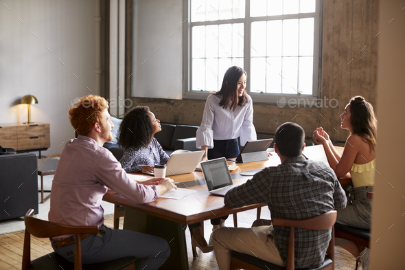 Young woman standing to address colleagues at a work meeting - Stock Photo - Images