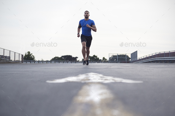 Male athlete running on a road towards camera, full length - Stock Photo - Images