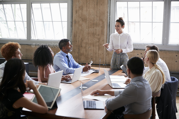 Female manager stands addressing team at board meeting - Stock Photo - Images
