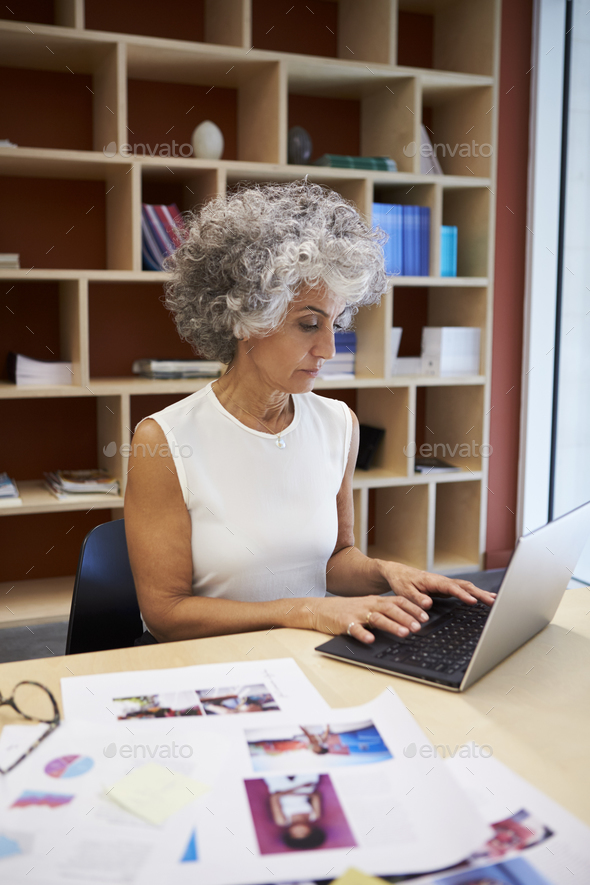 Senior businesswoman working on laptop in office, vertical - Stock Photo - Images