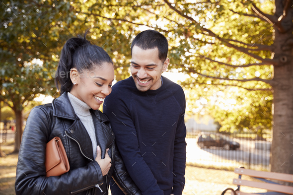Young Hispanic couple walking hand in hand in Brooklyn park - Stock Photo - Images