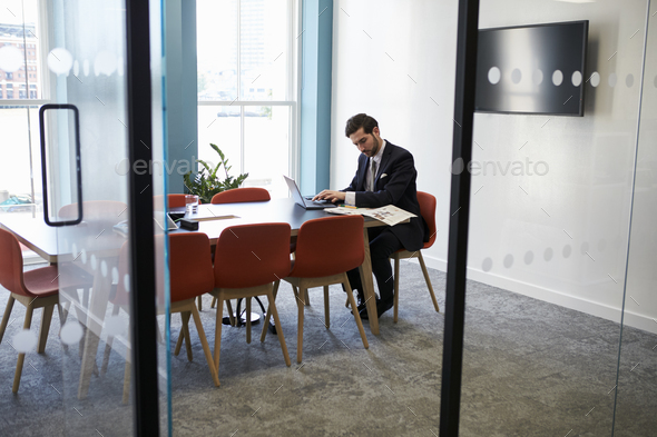 Young businessman working alone in a boardroom - Stock Photo - Images
