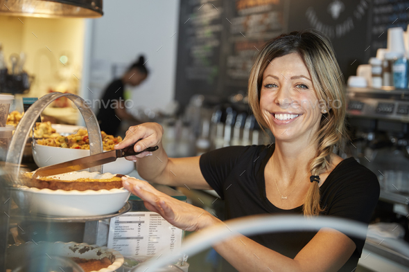 Waitress Behind Counter In Coffee Shop Cutting Slice Of Cake - Stock Photo - Images