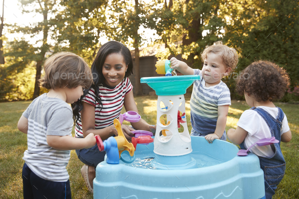 Mother And Young Children Playing With Water Table In Garden - Stock Photo - Images