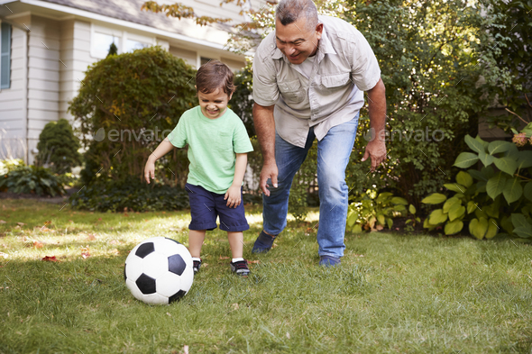 Grandfather Playing Soccer In Garden With Grandson - Stock Photo - Images