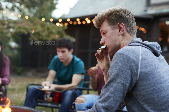 Teenage boy eating somore with friends at a fire pit - Stock Photo - Images