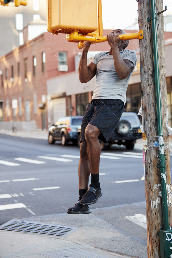 Young black man doing chin ups in Brooklyn street, vertical - Stock Photo - Images