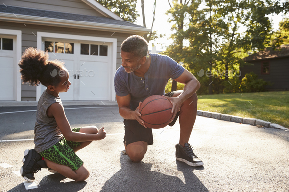 Father Teaching Son How To Play Basketball On Driveway At Home - Stock Photo - Images