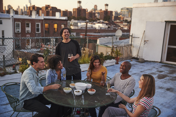 Six adult friends enjoying a party on a New York rooftop - Stock Photo - Images