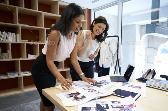Two female creatives discussing magazine layout in an office - Stock Photo - Images