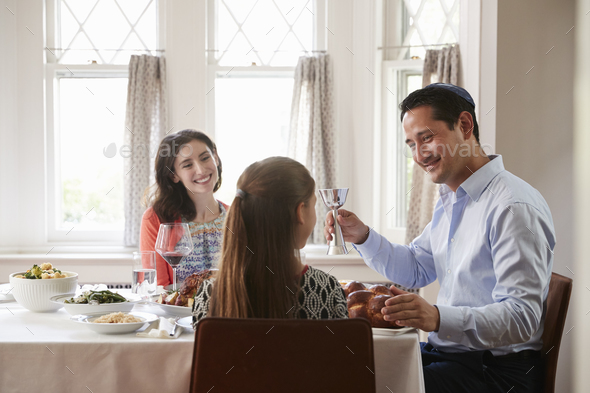 Jewish man holding kiddish cup blesses his family at Shabbat - Stock Photo - Images