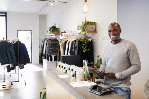 Male assistant smiling behind the counter in clothing store - Stock Photo - Images