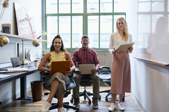 Three coworkers in a team meeting looking to camera - Stock Photo - Images