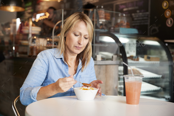 Woman In Coffee Shop Sitting At Table Eating Bowl Of Soup - Stock Photo - Images