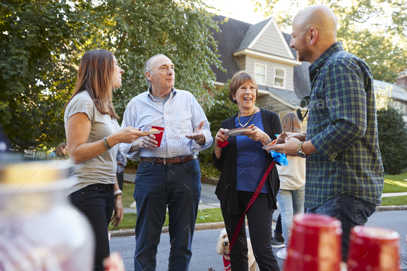 Middle aged and senior neighbours talking at a block party - Stock Photo - Images
