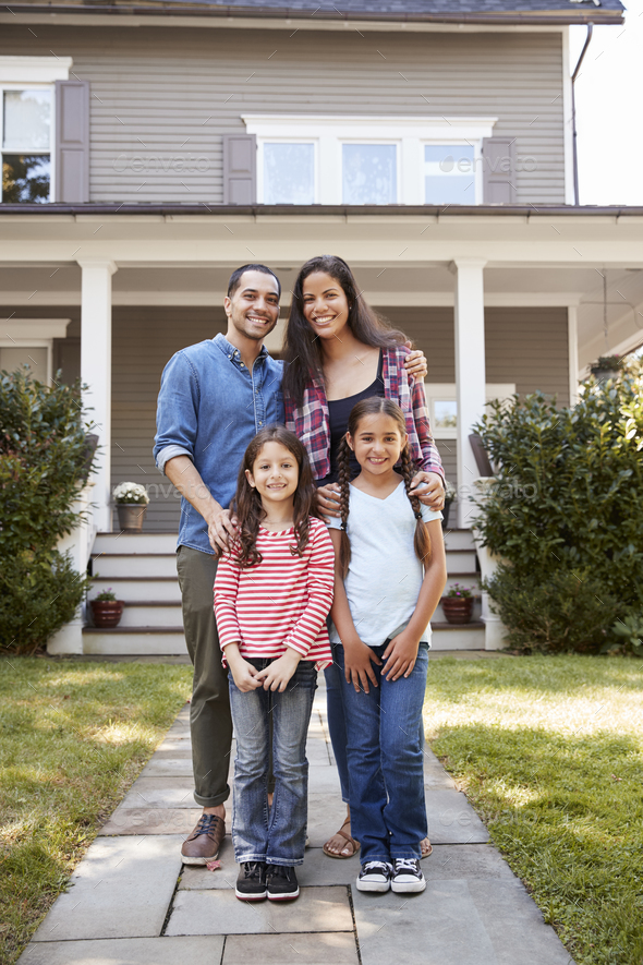 Portrait Of Smiling Family Standing In Front Of Their Home - Stock Photo - Images