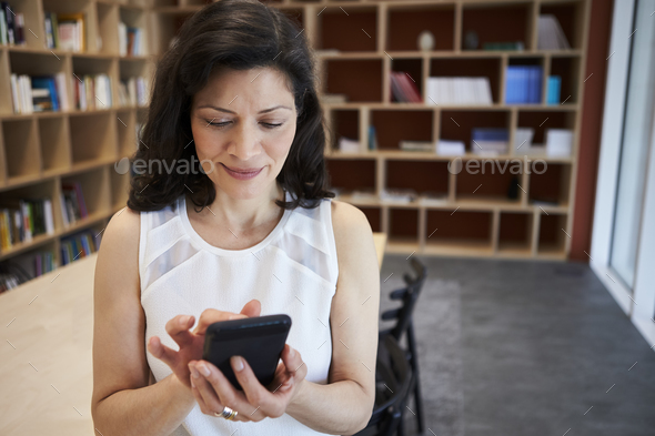 Middle aged female creative using smartphone in office - Stock Photo - Images