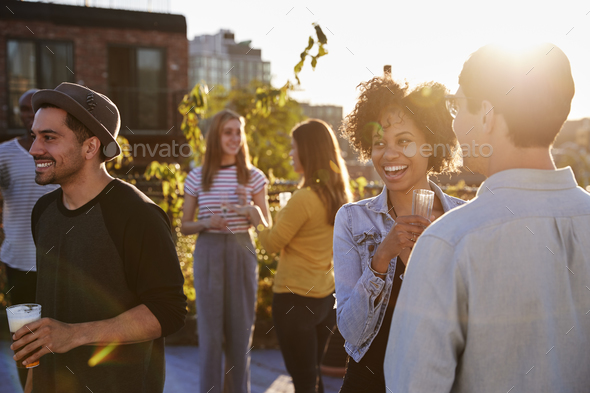 Happy friends at a rooftop party backlit by sunlight - Stock Photo - Images