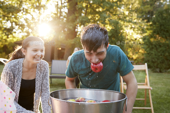 Teenage boy, apple in mouth, apple bobbing at garden party - Stock Photo - Images
